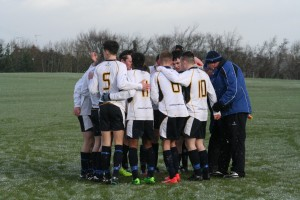 The 18s huddle before the game , tactics or cold.